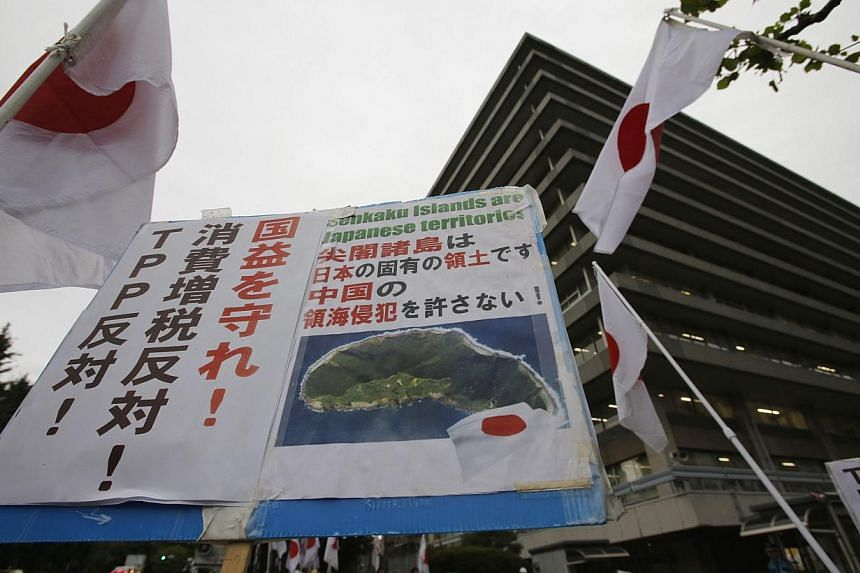 A member of the nationalist movement Ganbare Nippon holding a placard of disputed islands known as Senkaku in Japan and Diaoyu in China, among Japanese national flags during a rally in Tokyo on Sept 11, 2013. -- FILE PHOTO: REUTERS