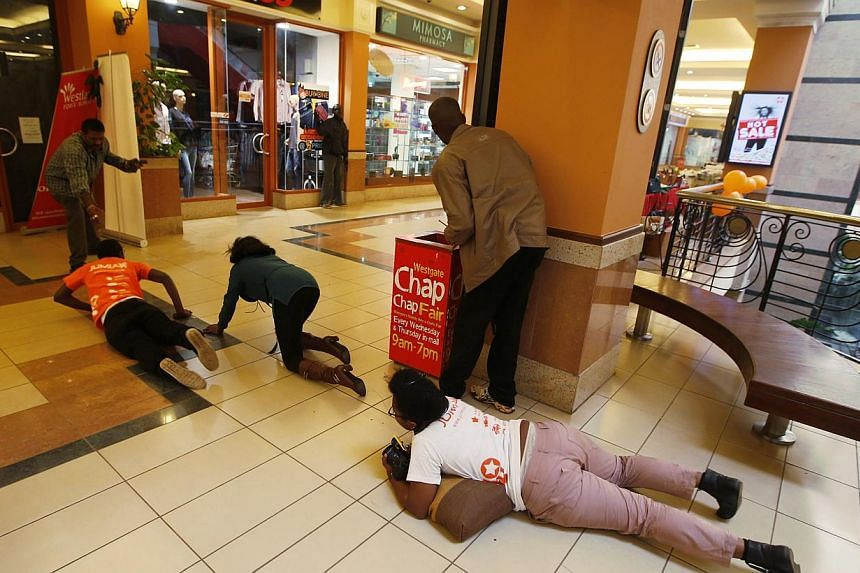People scramble for safety as armed police hunt gunmen who went on a shooting spree at Westgate shopping centre in Nairobi, September 21, 2013. The gunmen stormed a shopping mall in Nairobi on Saturday killing at least 20 people in what Kenya's gover