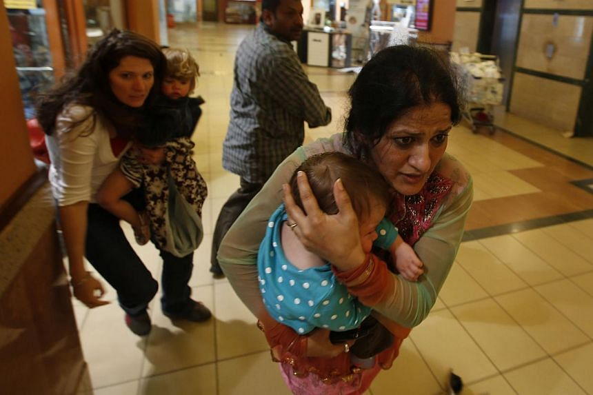 Women carrying children run for safety as armed police hunt gunmen who went on a shooting spree in Westgate shopping centre in Nairobi September 21, 2013. --PHOTO: REUTERS