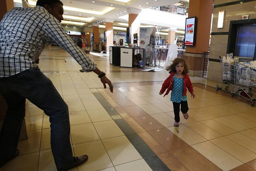 A child runs to safety as armed police hunt gunmen who went on a shooting spree at Westgate shopping centre in Nairobi September 21, 2013.--PHOTO: REUTERS