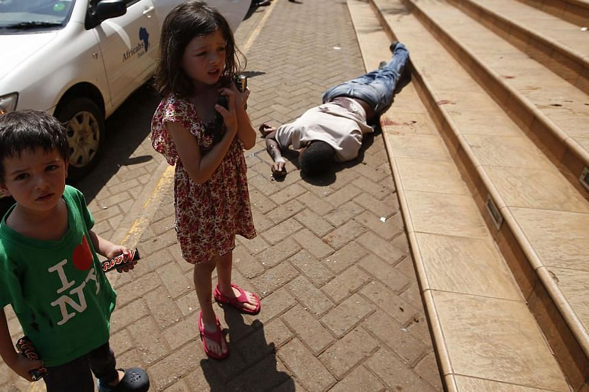 Terrified children wait by the body of a man after escaping from the Westgate shopping centre as police search for gunmen in Nairobi, September 21, 2013. --PHOTO: REUTERS