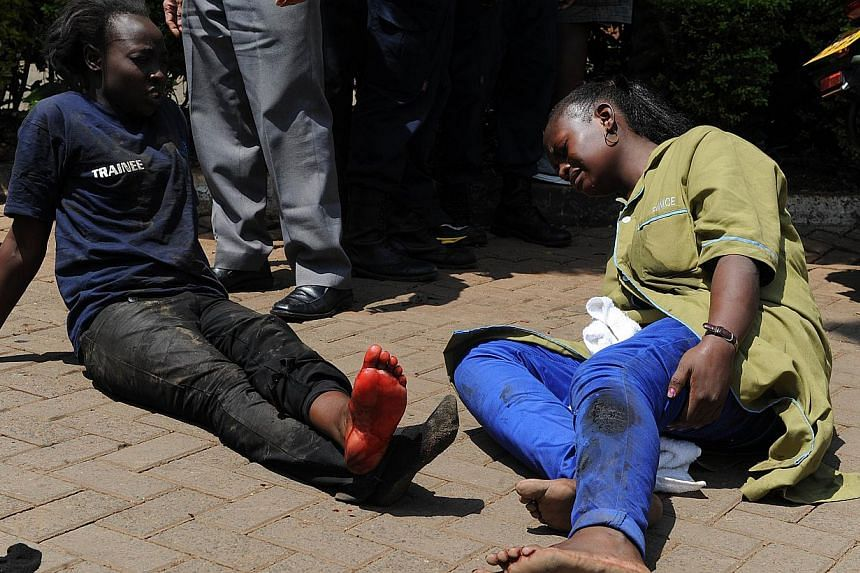 Injured people sit on the street waiting for assistance after masked gunmen stormed an upmarket mall and sprayed gunfire on shoppers and staff, killing at least thirteen on September 21, 2013 in Nairobi. --PHOTO: AFP