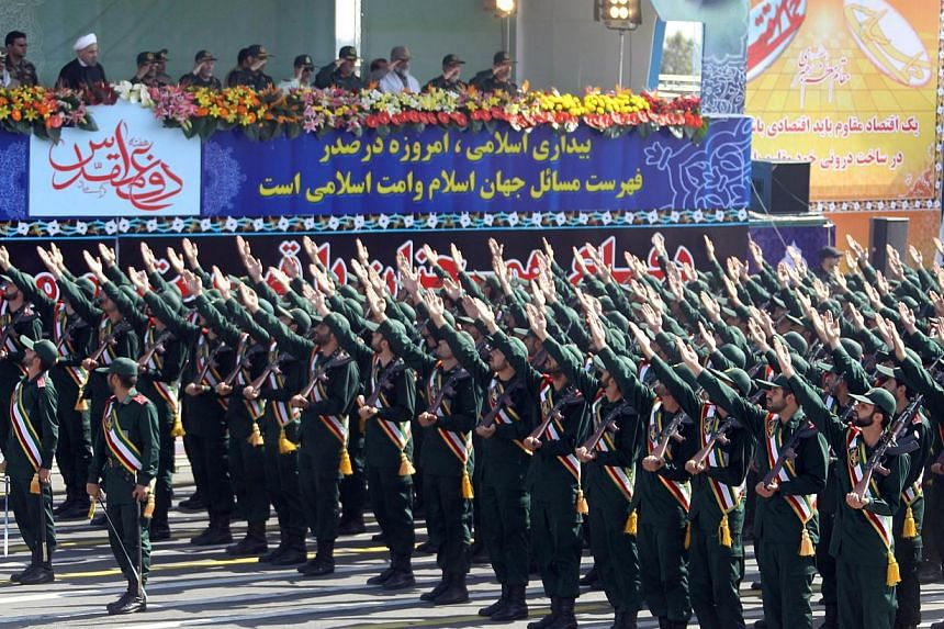 Members of Iran's elite Revolutionary Guards march past President Hassan Rowhani (left) and military officials during an annual military parade which marks Iran's eight-year war with Iraq, 1980-88, in the capital Teheran, on Sept 22, 2013. -- PHOTO:
