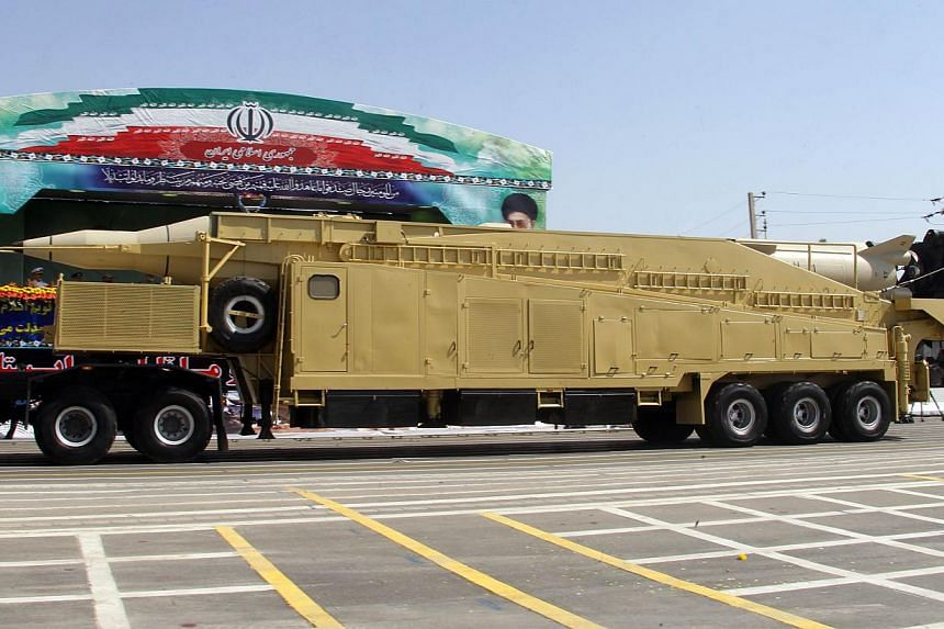 A military truck carries a Sejil medium-range missile past portraits of the Islamic republic's supreme leader, Ayatollah Ali khamenei (from right), and his predecessor, the late Ayatollah Ruhollah Khomeini, during an annual military parade which mark