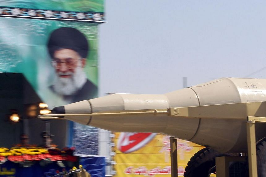 A military truck carries a Sejil medium-range missile past a large portrait of Iran's Supreme Leader Ayatollah Ali Khamenei, during an annual military parade which marks Iran's eight-year war with Iraq, in the capital Teheran, on Sept 22, 2013. -- PH