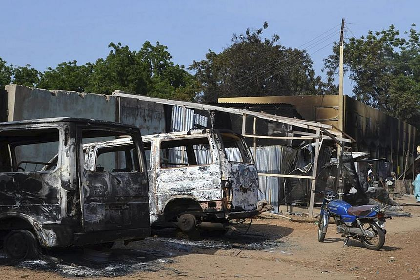 Burnt vehicles and houses are pictured on a street, after Boko Haram militants raided the town of Benisheik, west of Borno State capital Maiduguri Sept 19, 2013. The death toll from an attack in northeastern Nigeria that saw insurgents dressed as sol
