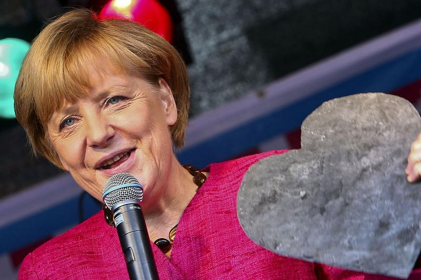 German Chancellor Angela Merkel holds a heart-shaped piece of slate she was given during an election campaign event of the Christian Democratic Union (CDU) party on Saturday, Sept 21, 2013 in Stralsund, eastern Germany. Germans began voting on Sunday