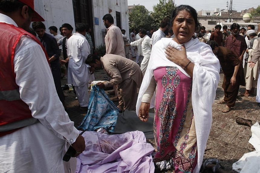 A woman mourns the death of her relative after two suicide bombers on Sunday killed at least 53 people and wounded more than 100 in an attack on a church service in the restive north-western Pakistani city of Peshawar, officials said. -- PHOTO: REUTE