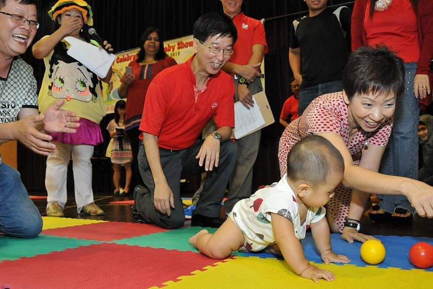 Minister in the Prime Minister's Office Grace Fu and People's Association (PA) chief executive director Ang Hak Seng (in red) at the launch of the PA's first information resource point for parents at Yuhua Community Centre. The PA will set up informa