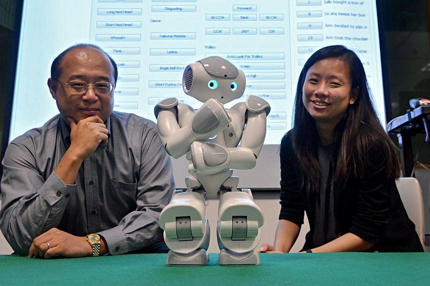 Associate Professor Chen I-Ming (above, left) and senior psychologist Goh Tze Jui with NAO the robot. -- ST PHOTO: NURIA LING