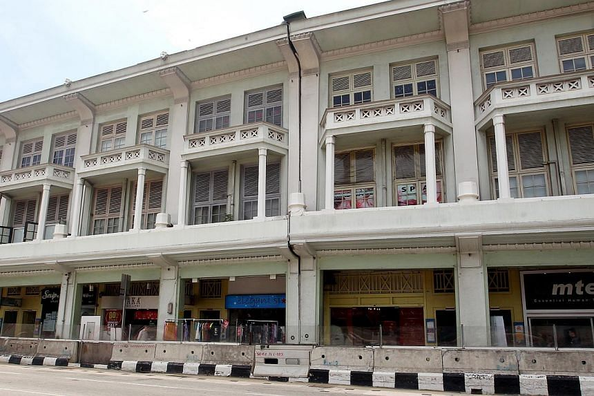 The facade of Bugis Village (left) has a large and very visible crack running from the roof (inset) all the way down to the ground level.