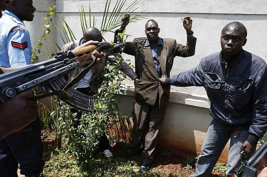 Policemen search a man for weapons as he walked out of Westgate Shopping Centre in Nairobi September 21, 2013. Three Britons have been confirmed killed in an armed attack on a shopping mall in Nairobi and the number is likely to rise, Britain's Forei