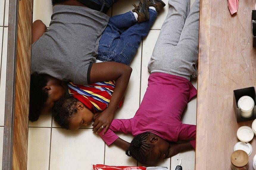 A mother and her children hide from gunmen at Westgate Shopping Centre in Nairobi, Sept 21, 2013. -- PHOTO: REUTERS