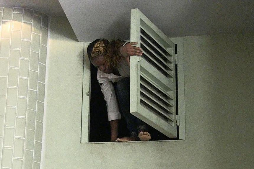 An image grab taken from AFP TV shows a Kenyan woman coming out of an air vent where she was hiding during an attack by masked gunmen at a shopping mall in Nairobi on Sept 21, 2013. -- PHOTO: AFP