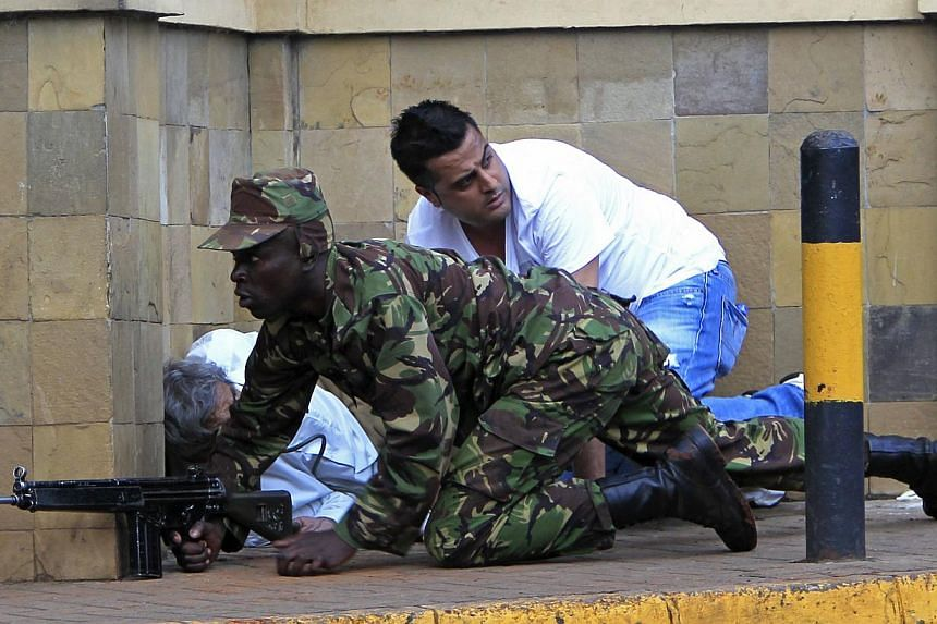 A Kenyan army soldier takes cover behind a wall at Westgate Shopping Centre in Nairobi, Sept 21, 2013. -- PHOTO: REUTERS