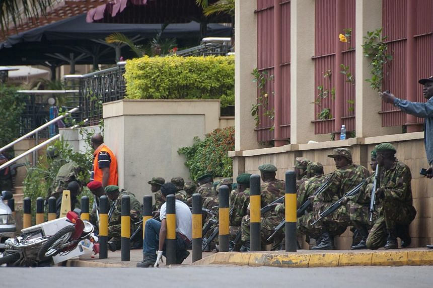 Armed police crouch down and take position during a gun battle outside the Westgate Mall in Nairobi, Kenya Saturday, Sept 21, 2013. -- PHOTO: AP