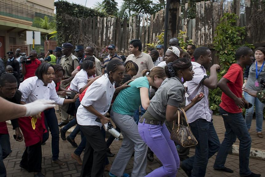 Civilians who had been hiding inside during the gun battle manage to flee from the Westgate Mall in Nairobi, Kenya Saturday, Sept 21, 2013. -- PHOTO: AP