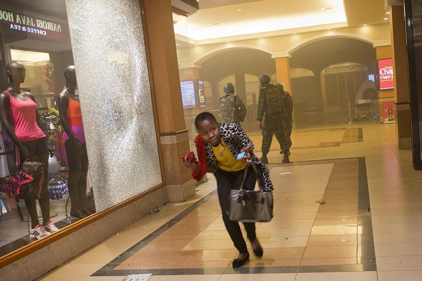 A woman who had been hiding during the gun battle runs for cover after armed police, seen behind, enter the Westgate Mall in Nairobi, Kenya, Saturday, Sept 21, 2013. -- PHOTO: AP