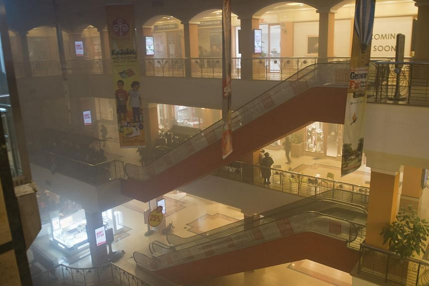 Armed police take cover behind escalators as smoke fills the air inside the Westgate Mall in Nairobi, Kenya Saturday, Sept 21, 2013. Masked gunmen stormed a packed upmarket shopping mall in Nairobi on Saturday, killing 39 people and wounding 150 more