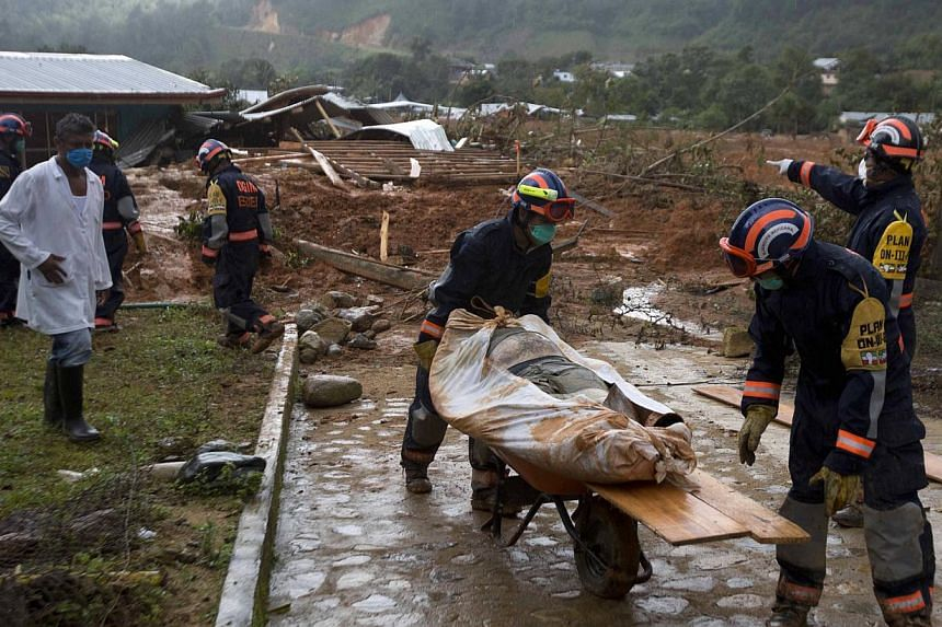 Soldiers remove a body recovered from the site of a landslide in La Pintada, Mexico, Saturday, Sept 21, 2013.Mexico looked Saturday to the Herculean task of rebuilding after a rare double onslaught of storms, with nearly 170 people feared dead in the