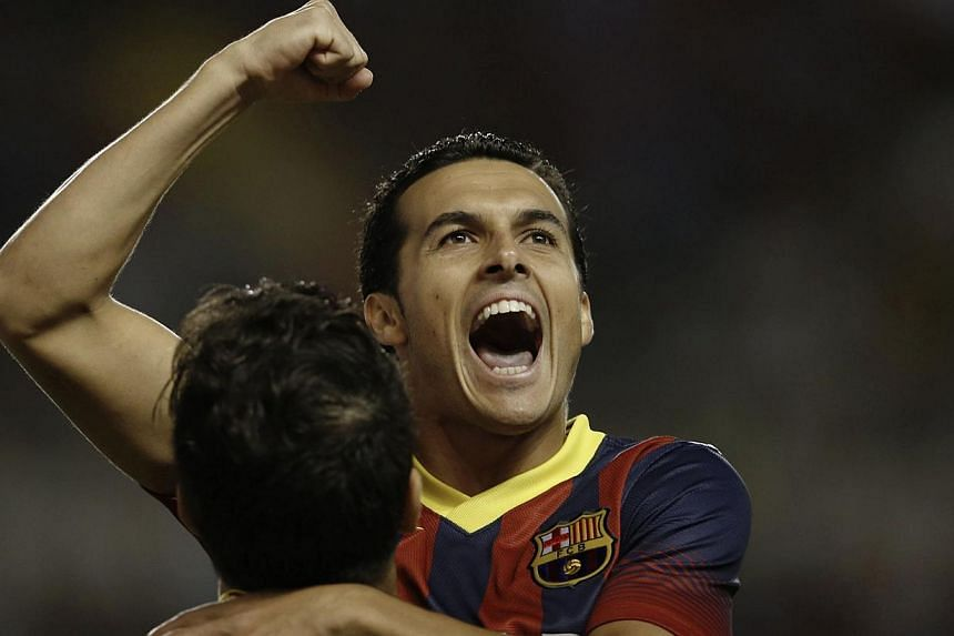Barcelona's Pedro Rodriguez celebrates his second goal with team mate Cesc Fabregas during their Spanish First Division soccer match against Rayo Vallecano at Vallecas stadium in Madrid, Sept 21 , 2013. Pedro Rodriguez scored a hat-trick as Barcelona