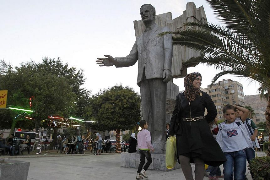 Syrians walk past a large statue of Hafez al-Assad, the father of current Syrian President Bashar, at a park in the capital Damascus, on Sept 21, 2013. Syria has handed over complete data on its chemical arsenal to the world's watchdog, meeting a Sat