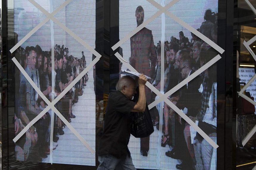 A man walks past the windows of a boutique store that have been taped-up in preparation for Typhoon Usagi at Tsim Sha Tsui shopping district in Hong Kong, Sept 22, 2013. Singapore Airlines has urged its customers booked on flights in and out of Hong
