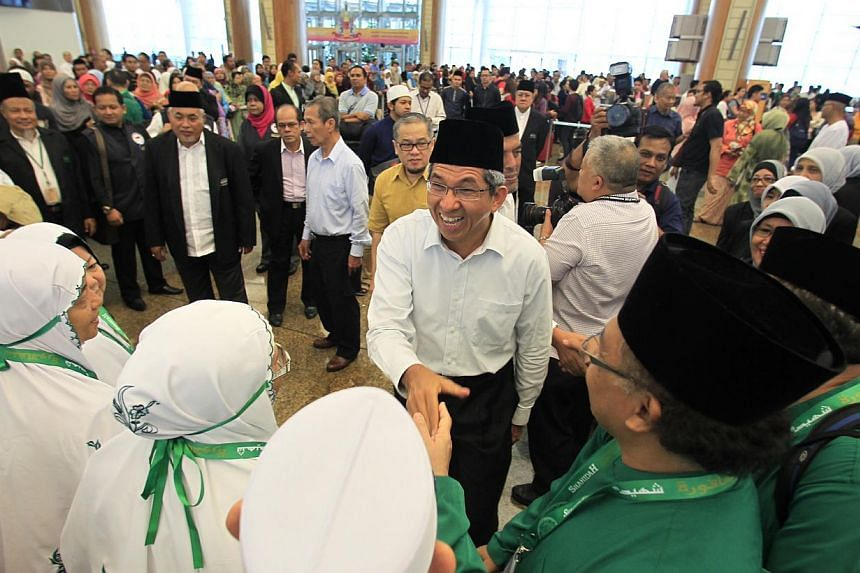 Minister for Muslim Affairs Yaacob Ibrahim with pilgrims embarking on their Haj pilgrimage at Changi Airport on Sunday, Sept 22, 2013. -- ST PHOTO: KEVIN LIM