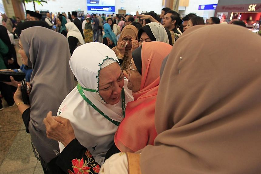 It was an emotional farewell for pilgrims as they embarked on their Haj pilgrimage at Changi Airport on Sunday, Sept 22, 2013. -- ST PHOTO: KEVIN LIM