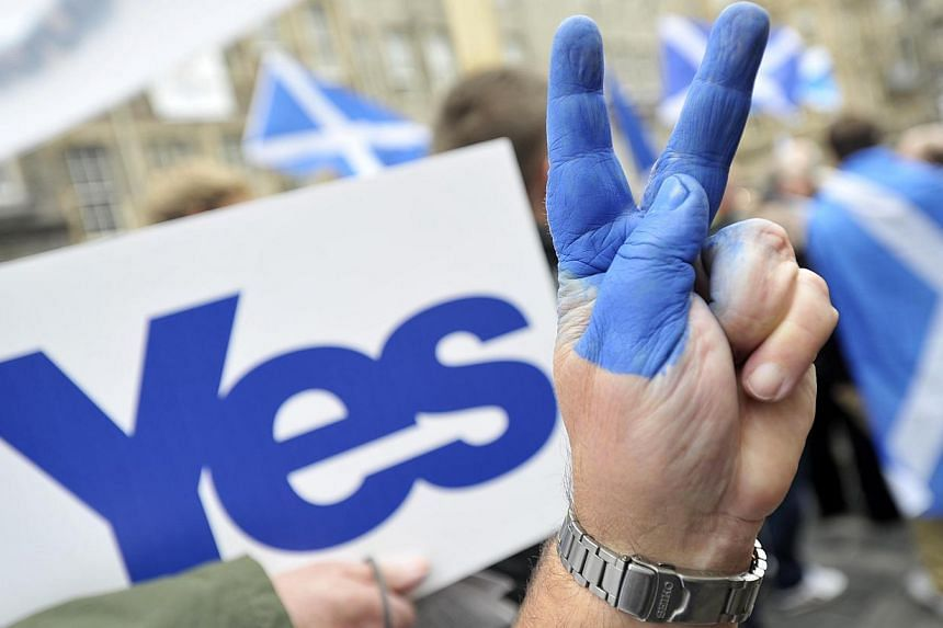 A Pro-independence supporter flashes the victory sign as people gather in Edinburgh on Sept 21, 2013 for a march and rally in support of a yes vote in the Scottish Referendum to be held on Sept 18, 2014. -- PHOTO: AFP