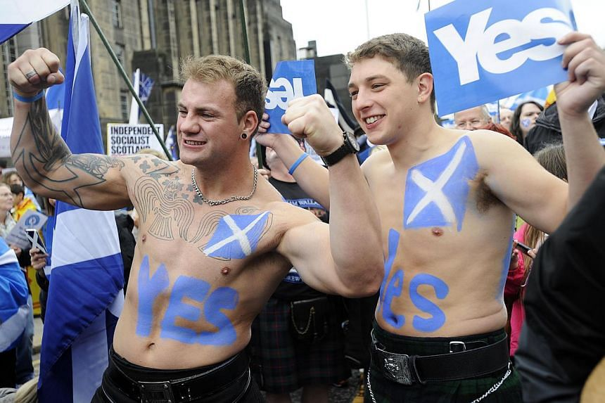 Pro-independence supporters wearing kilts pose for photographs as people gather for a rally in Edinburgh on Sept 21, 2013. -- PHOTO: AFP