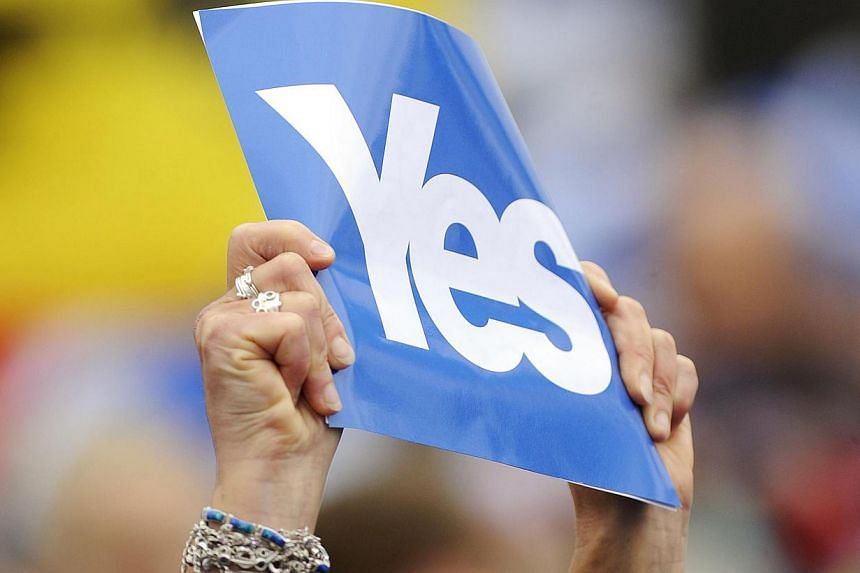 "A pro-independence supporter holds up a ""Yes"" placard during a march and rally in Edinburgh on Sept 21, 2013 in support of a yes vote in the Scottish Referendum to be held in Sept 2014. -- PHOTO: AFP"