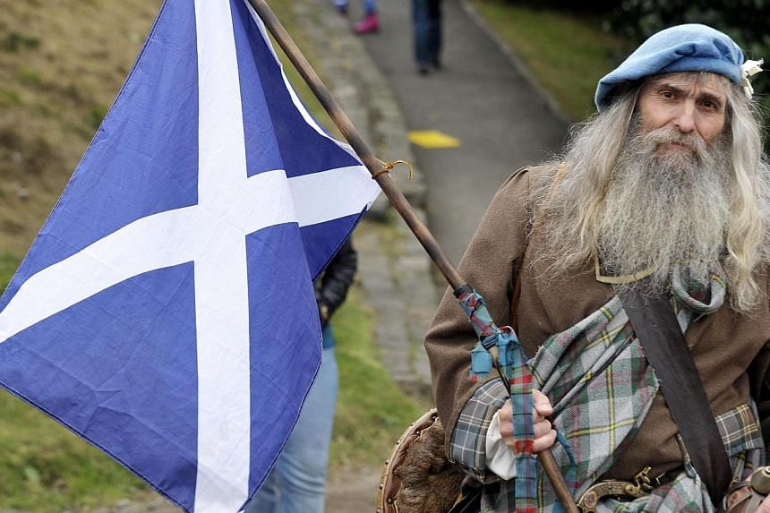 A Pro-independence supporter wearing a kilt holds the Scottish flag as people gather for a rally in Edinburgh on Sept 21, 2013. -- PHOTO: AFP