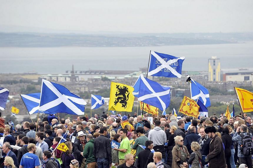 Pro-independence supporters wave the Saltire as they gather in Edinburgh on Sep 21, 2013 for a march and rally in support of a yes vote in the Scottish Referendum to be held in Sept 2014. -- PHOTO: AFP