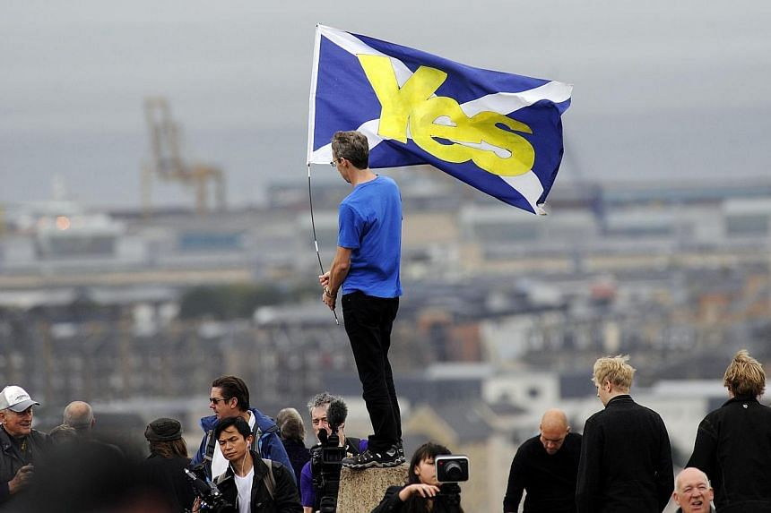 "A pro-independence supporter holds a Saltire flag with ""Yes"" written on it in Edinburgh on Sept 21, 2013 during a march and rally in support of a yes vote in the Scottish Referendum to be held in Sept 2014. -- PHOTO: AFP"