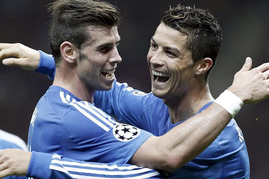 Real Madrid's Cristiano Ronaldo (centre) celebrates a goal with team mate Gareth Bale against Galatasaray during their Champions League Group B soccer match at Turk Telekom Arena in Istanbul September 17, 2013. Real Madrid shrugged off a warm-u