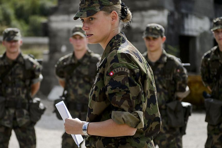 A captain of the rescue troops of the Swiss Army stands with aspirant-officiers on September 19, 2013, in Epeisse near Geneva. Switzerland's voters on Sunday rejected a plan to axe the country's military draft, bucking Europe's anti-conscription