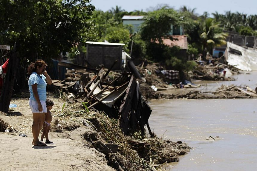 A woman and a child stand near destroyed houses in Coyuca de Benitez, in the Mexican state of Guerrero, September 21, 2013. Still reeling from storms that killed more than 170 people in Mexico, Acapulco has evacuated thousands of tourists but no