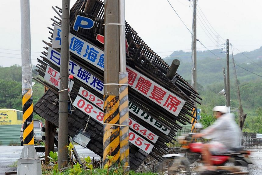 A motorcyclist ride pass a damaged billboard blown over by strong winds in Typhoon Usagi in Taiwan's Hangtsun, Pingtung county, on Sept 22, 2013.Typhoon Usagi has left 25 people dead in southern China's Guangdong province, state media reported