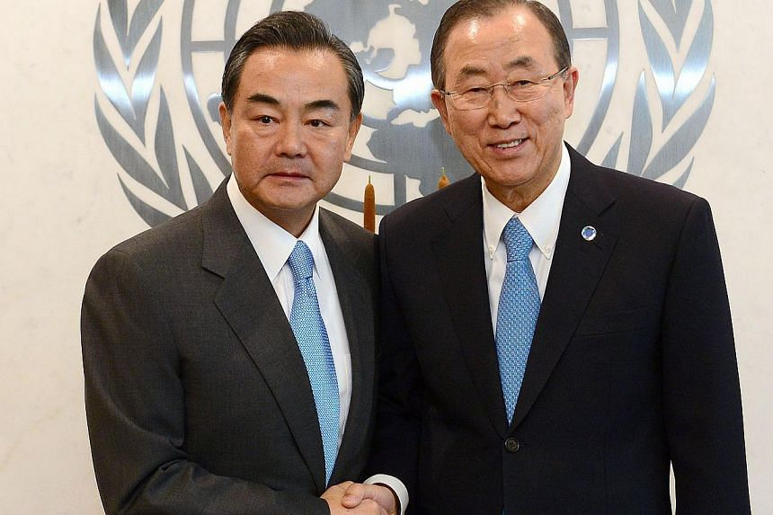 UN Secretary General Ban Ki Moon greets Chinese Foreign Minister Wang Yi at the United Nations headquarters prior to the start of the UN general assembly, in New York, Sept 22, 2013. China's Foreign Minister Wang Yi told UN Secretary General Ban Ki M
