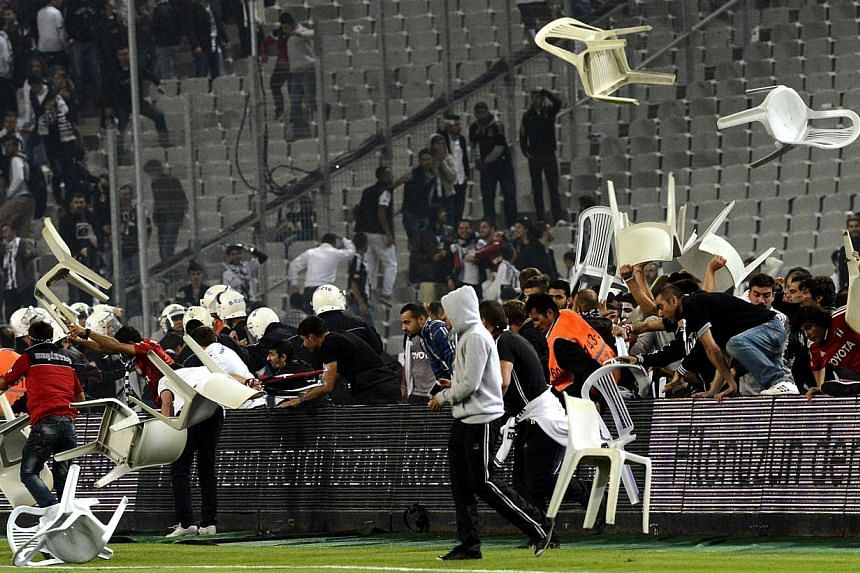 Besiktas football team supporters fight with Anti riot police officers during the Turkish super league football match Besiktas vs Galatasaray on September 22, 2013, at the Ataturk stadium in Istanbul. The high-profile Istanbul derby between bit