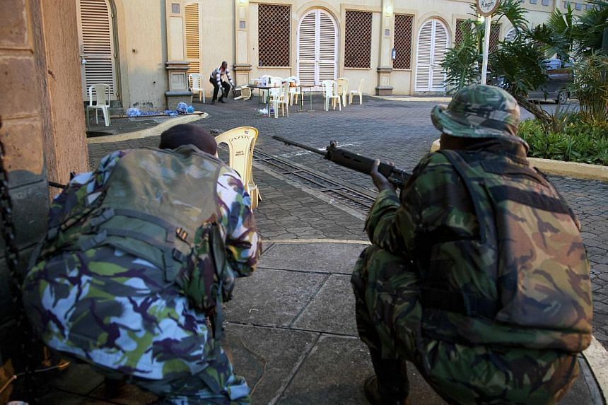 Kenya security personnel take cover outside the Westgate Mall after shooting started inside the mall early Monday morning, Sept. 23, 2013.Somali Al-Shabab militants have threated to kill hostages they are holding in a Nairobi shopping mall as K