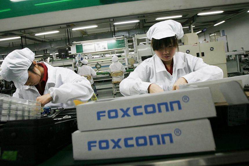 Employees work inside a Foxconn factory. Eleven workers at Taiwan's Foxconn, which assembles products for Apple and other tech companies, were injured during a brawl near its plant in eastern China, the company said on Monday, Sept 23, 2013. -- FILE