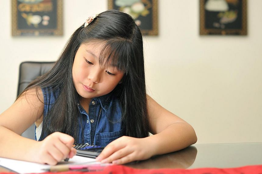 "Twelve-year-old Christie Ko is a straight-A student who has tuition in Chinese, Maths and English. ""If I don't work hard, my grades will fall,"" she says. -- PHOTO: LIM YAOHUI FOR THE STRAITS TIMES"