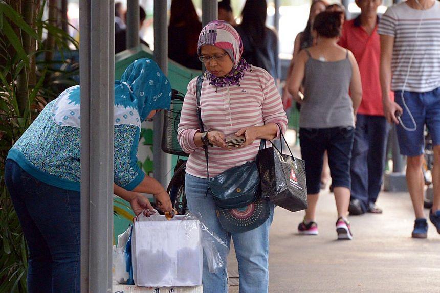 Madam Yanti (left) selling curry puffs outside an MRT station.