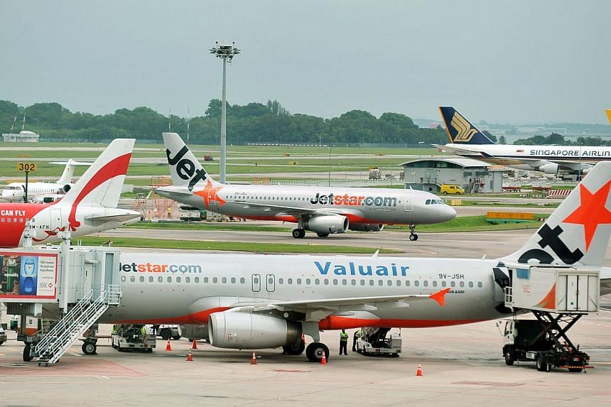 A Jetstar Airbus A320 plane at the Changi Airport Terminal 1 on Sept 21, 2011. Singapore's competition watchdog has no issues with Jetstar carriers working closely to plan flight schedules for example.-- ST FILE PHOTO:ALPHONSUS CHERN