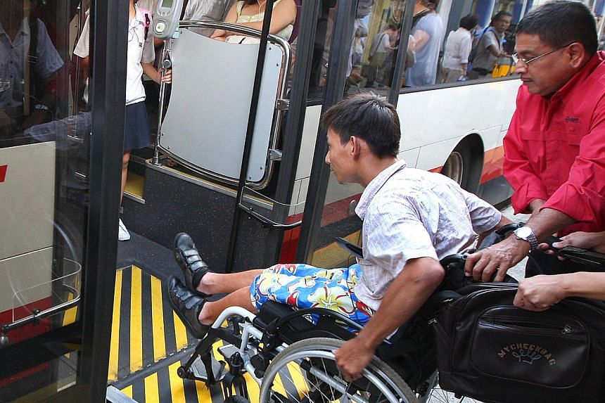 SMRT bus driver Machap Simakarupm helping Mr Patrick Ang to board the bus. SMRT is introducing wheelchair-friendly buses on four more bus services, bringing the total number of wheelchair-accessible bus services run by the operator to 38. -- TNP FILE