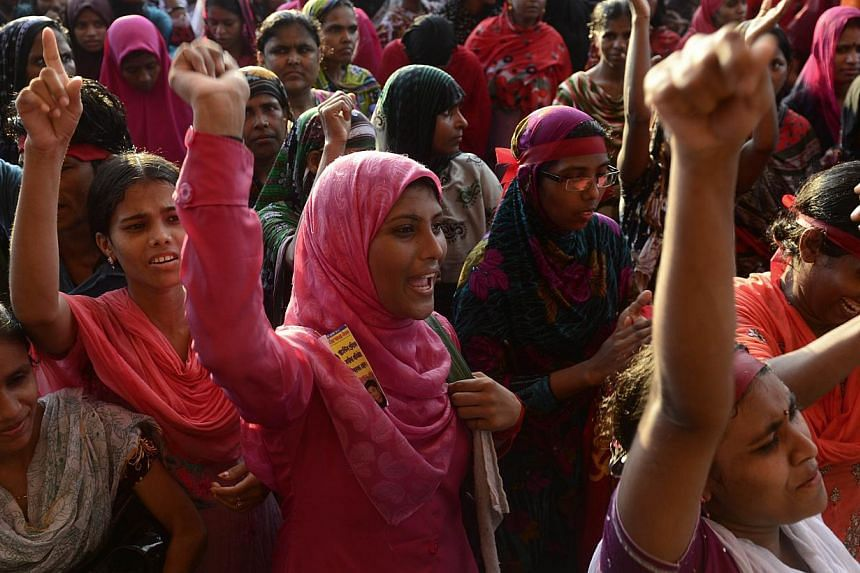 Bangladeshi garment workers shout slogans during a protest on wage increases in Dhaka on Sept 21, 2013. Angry Bangladeshi garment workers blocked roads, set factories alight and clashed with police for a third day as protests demanding a minimum mont