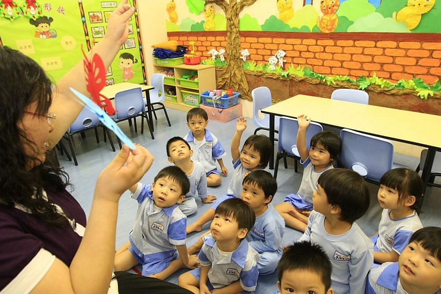 Preschool educator from Just Kids Learning Place, Ms Lu Xiu Ye, with the kids at the childcare centre. The Government is setting aside $40 million over the next five years to help small and mid-sized pre-school operators setting up in high-demand are
