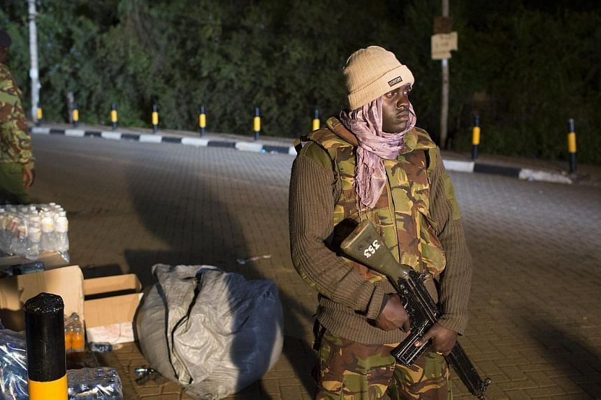 Police officers guard the edge of a security perimeter put into place a distance from the Westgate Shopping Centre in Nairobi, in the early hours of the morning during a standoff operation between Kenyan security forces and gunmen inside the building